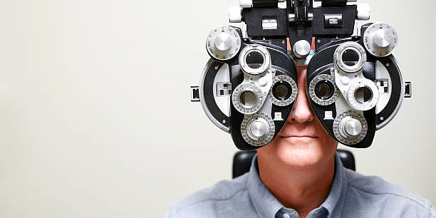 Mature man looking through Ophthalmic Instrument called a phoroptor.